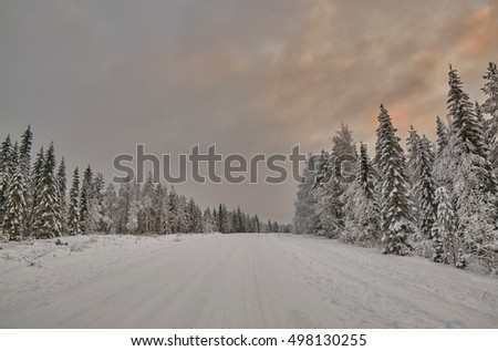 Scenic warm-Colored Sunset over Finnish Road after snow storm blizzard