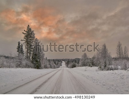 Scenic warm Coloured Sunset over Finnish Road after snow blizzard