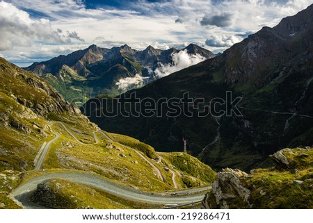 Scenic winding road in alpine valley at sunset with dramatic sky and great view. Piedmont, Italian Alps. - stock photo