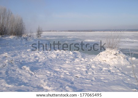 Scenic winter landscape beneath the ice reservoir wonderful blue sky fog and frost on the trees on the shore - stock photo