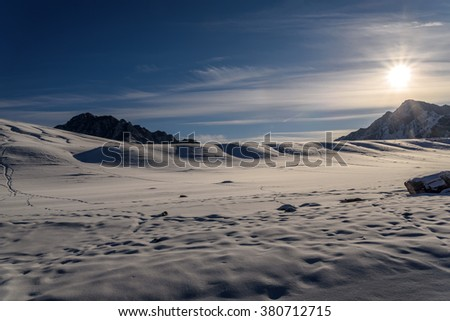 Scenic winter landscape with mountains covered with snow and the sun on a background of blue sky and clouds - stock photo