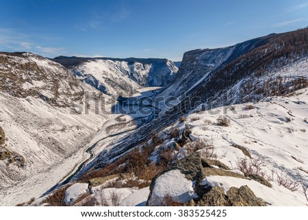 Scenic winter top view on the mountains covered with snow and forests, the valley between the mountains with a winding river and a steep winding road leading down - stock photo