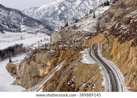 Scenic winter top view on the mountains covered with snow, trees, asphalt winding road between the mountains and the valley - stock photo