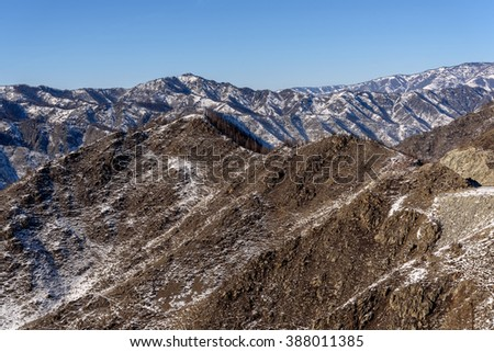 Scenic winter view on the mountains, mountain slopes are covered with snow and trees on a background of blue sky - stock photo