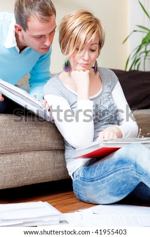 Scenic young family couple at home indoors in living room doing paperwork sitting on couch and floor with lot of paper documents - stock photo