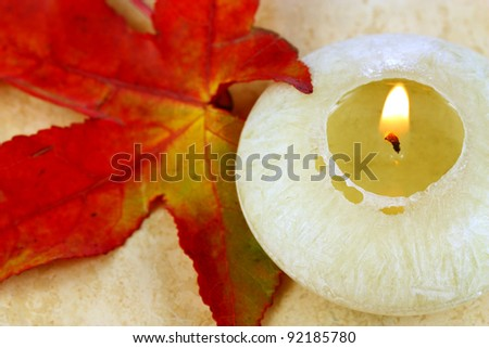 Scented candle and red colored autumn leaf of amber tree