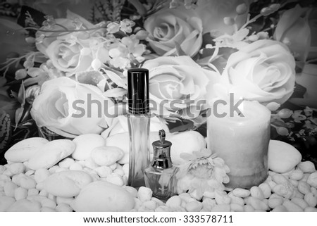 scented candles and cosmetic container with blur bunch of fabric roses in vintage tone background ,black and white tone - stock photo