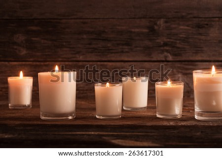 scented candles on old wooden background - stock photo
