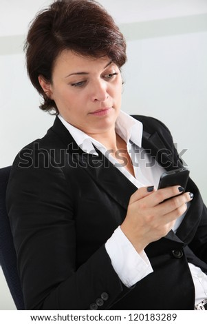 Sceptical businesswoman reading a text message on her mobile phone and raising her eyebrow in disbelief - stock photo