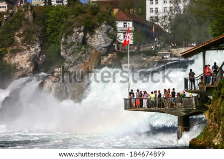 SCHAFFHAUSEN -APR 10: tourists at Rheinfall observation deck on April 10th, 2011 in Schaffhausen. Switzerland. Rheinfall is the biggest waterfall in Europe located on Switzerland and Germany border. - stock photo