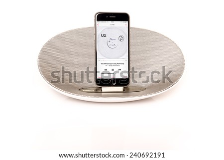 SCHARNHAUSEN, GERMANY - DECEMBER 29,2014: Front view of an Apple iPhone 6 in a Philips docking station and speaker playing the U2 album Songs Of Innocence with reflection on a white background on - stock photo
