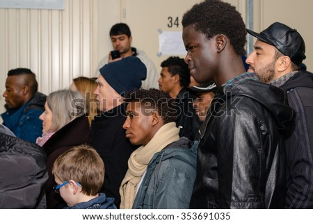 SCHARNHAUSEN, GERMANY - DECEMBER 20, 2015: Refugees from Libya, Nigeria, Afghanistan, Pakistan, Eritrea, Gambia, Togo, Algeria, Tunisia and other countries are listening to the Christian Christmas - stock photo