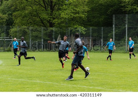 SCHARNHAUSEN, GERMANY - MAY 14, 2016: The team of TSV Scharnhausen is playing a friendly match of soccer against a team of refugees that is residing in a camp in Scharnhausen for 6 months now. Since a - stock photo