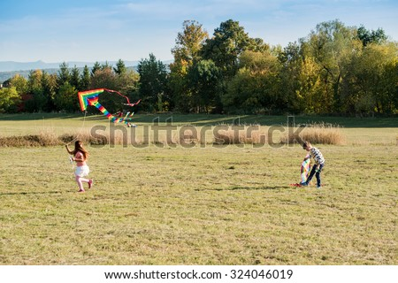 SCHARNHAUSEN, GERMANY - OCTOBER 3, 2015: Two cute little children are flying a kite in a meadow on a sunny autumn day. - stock photo