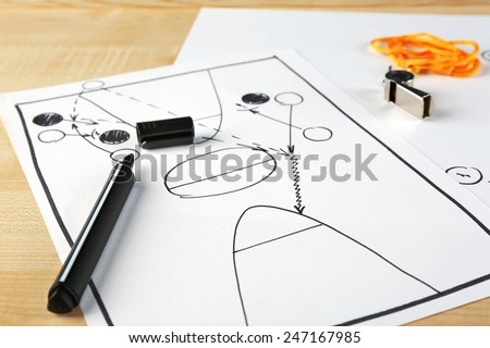 Scheme basketball game on sheet of paper and wooden table background - stock photo
