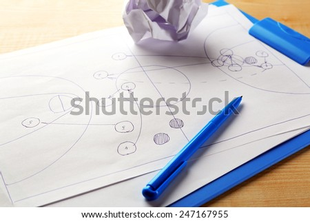 Scheme football game on clip board paper with crumpled ball and pen on wooden table background - stock photo