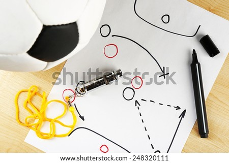 Scheme football game on sheet of paper and wooden table background - stock photo