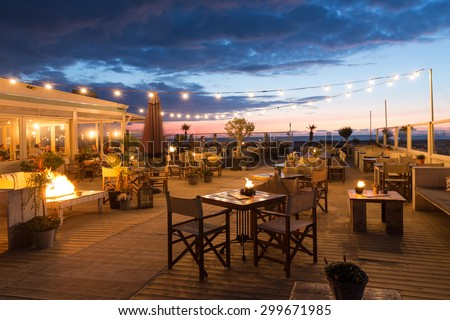 SCHEVENINGEN, THE NETHERLANDS - APR 30:  Sea sunset with eating people in a restaurant with terrace along the Dutch coast on April 30, 2015 Scheveningen, The Netherlands - stock photo
