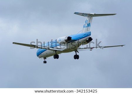 Schiphol, Noord-Holland/Netherlands- November 20-11-2015 -Plane from KLM Cityhopper PH-KZB Fokker F70 is landing at Schiphol Airport. Photo taken during a dark cloudy autumn day.