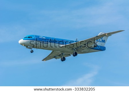 Schiphol, Noord-Holland/Netherlands- October 31-10-2015 -Plane from KLM Cityhopper  PH-KZO Fokker F70 is started landing at Schiphol Airport. Nice blue sky at the background of the Airplane.