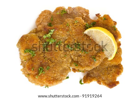 Schnitzel, garnished with lemon and parsley, isolated on white. - stock photo