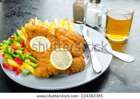 Schnitzel with french fries, homemade, platter, czech beer, vegetable, lemons - stock photo