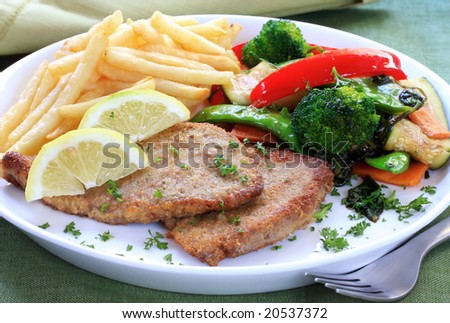 Schnitzel with fries and colorful vegetables.  Could be chicken, veal, or fish.