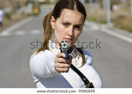 Scholar girl pointing at camera with gun - stock photo