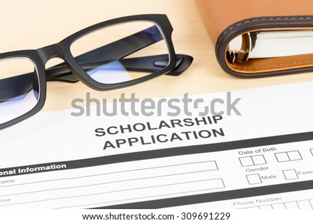 Scholarship application form with glasses - stock photo