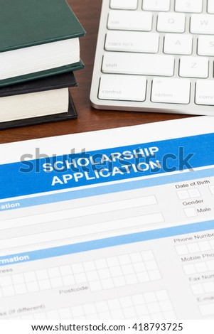 Scholarship application form with keyboard, and text book - stock photo