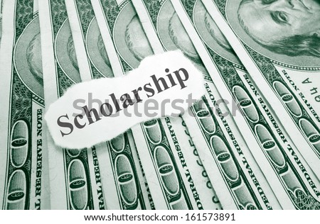 Scholarship text on paper, over hundred dollar bills                                - stock photo
