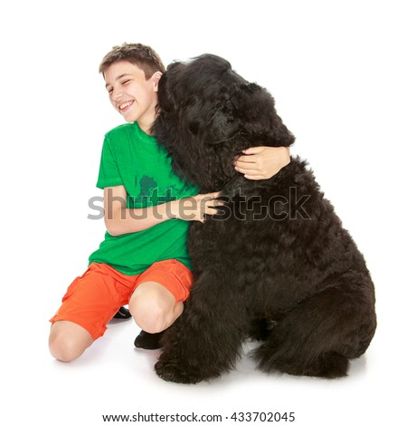 School-age boy hugging a large, shaggy black dog-Isolated on white background - stock photo