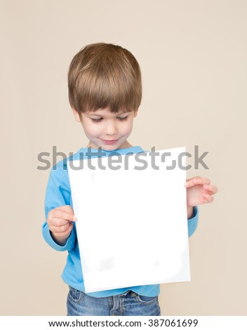School age child holding a blank page, picture, sign or homework for copyspace. Education and learning concept