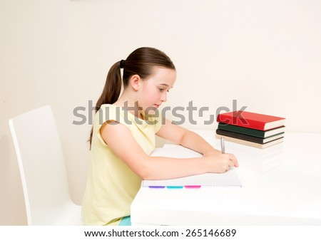 School age girl studying home work on white table on a white chair - stock photo