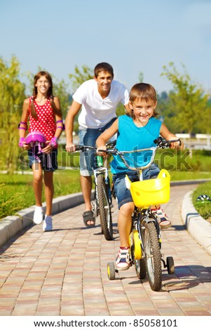 School aged boy and his father cycling, cheerful girl running behind - stock photo