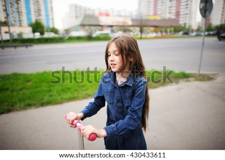 School aged little girl in dress on the scooter in the city street - stock photo