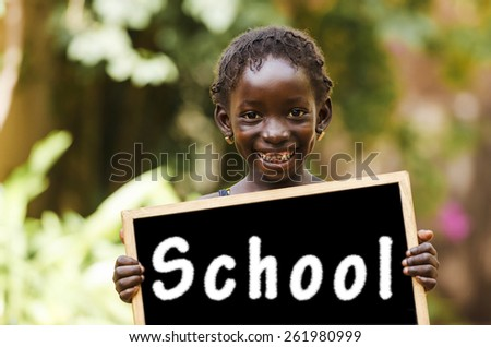 School And Education - African Girl Holding Chalkboard. An African teenage girl holding a chalkboard. - stock photo