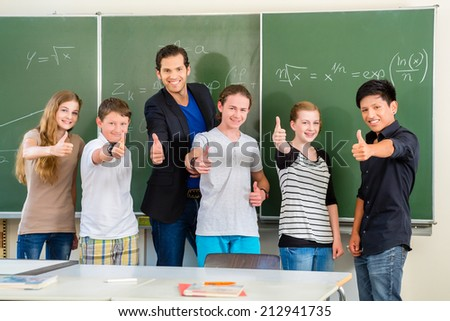 School and education - Teacher and students stand in front of a blackboard with math work in a classroom or class  - stock photo
