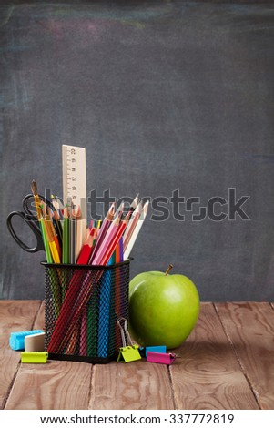 School and office supplies and apple on classroom table in front of blackboard. View with copy space - stock photo