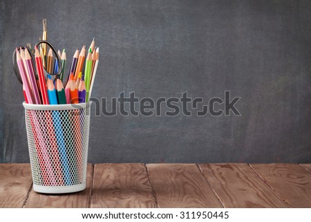School and office supplies on classroom table in front of blackboard. View with copy space - stock photo