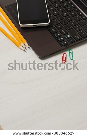 School and student supplies with closed slim notebook and smartphone on a white wooden table surface - stock photo