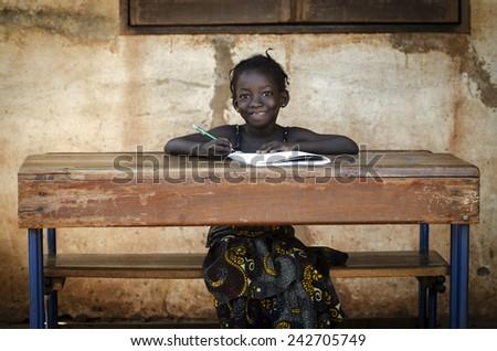 School Background: Proud African Schoolgirl Sitting In Her Desk Smiling - stock photo