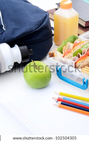 School bag, healthy lunch box and apple with books and pencil - stock photo