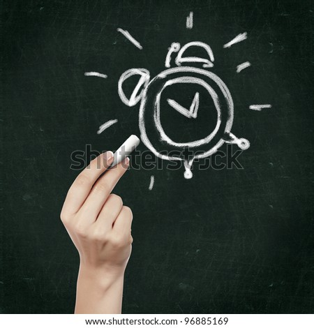 School blackboard and hand with chalk drawing alarm clock - stock photo