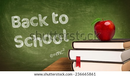 school books and apple against blackboard