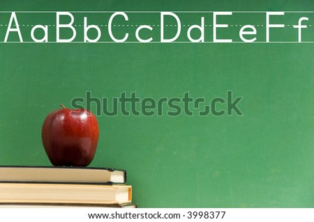 School books and apple in front of school chalkboard, with alphabet