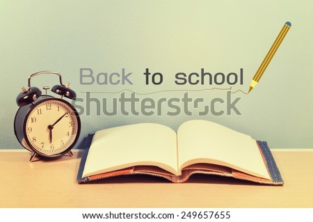 """school books and clock with """"back to school"""" on background - stock photo"""