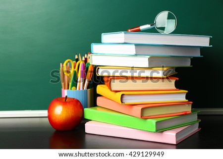School books on desk near chalkboard - stock photo
