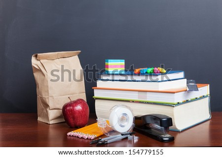 School books with apple and  paper bag lunch on desk in front of a blank chalkboard. - stock photo