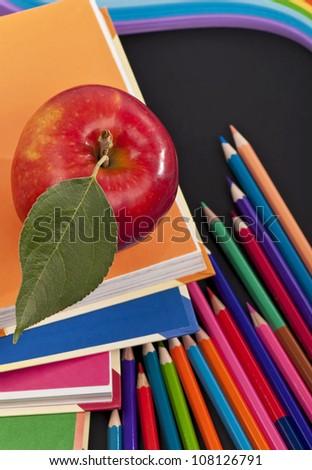 School books with apple on desk - stock photo